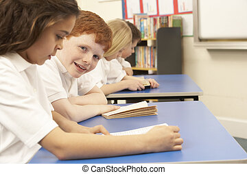 Group Of Children Reading Books In Classroom