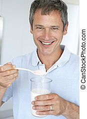 Middle Aged Man Holding Dietary Supplements