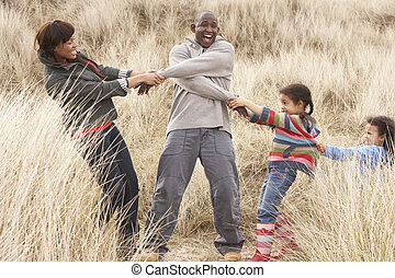 Family Having Fun In Sand Dunes