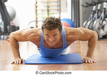 Man Doing Press Ups In Gym