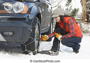 Woman Putting Snow Chains Onto Tyre Of Car