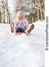 Girl Sledging Through Snowy Woodland