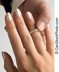 Man Putting Diamond Ring On Woman's Finger