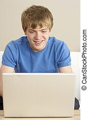 Young Boy Using Laptop At Home