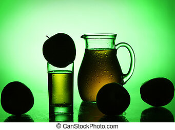 Fresh and cold apple juice in green spotlight