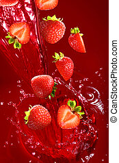 Strawberry falling into the lot of juice