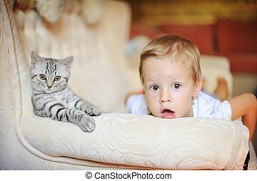 The kid and cat on a white sofa look forward