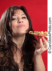 Mmmm woman enjoying pizza - A woman with dark brown hair is...