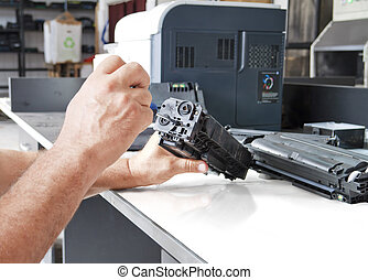 hands repairing toner cartridge - hands repairing laser...