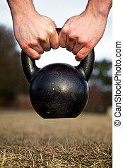 Hands holding a kettlebell - Closeup of hands lifting a...