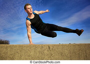 Parkour jump - Young man jumping over wall on obstacle...