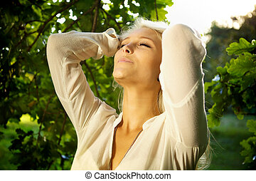Indulgence - Woman standing amongst trees and relaxing