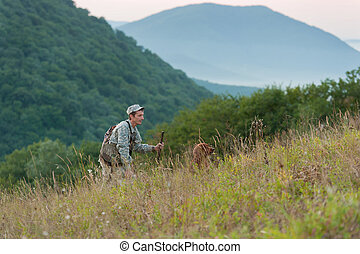 Hunter with dog in countryside - Hunter or soldier in khaki...