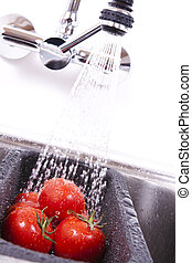 Delicious ripe tomatoes are washed off. - Kitchen faucet in...