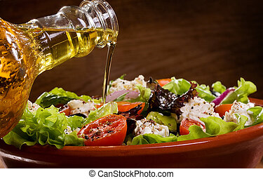 greek salad with olive oil pouring from a bottle