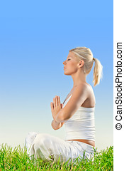 pretty young woman doing yoga meditation exercising outdoors...