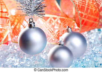 christmas silver baubles with red ribbon on ice