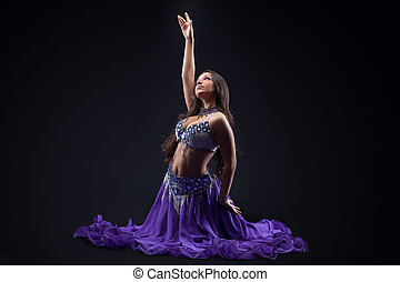 arabia dancer posing in dark - oriental costume