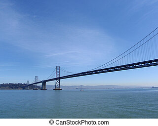 San Francisco side of Bay Bridge from boat sailing underneath on a clear day. with Yerba Buena island in view