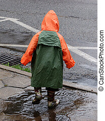 Boy play in rain. - Little kid playing in puddle on a street