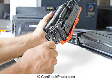 hands repairing toner cartridge - hands repairing laser...