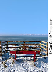 seasonal snowy frost covered red bench sea view