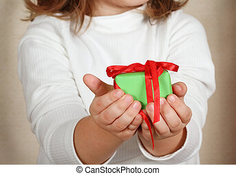 Little hands of the child holding Christmas present. Retro...