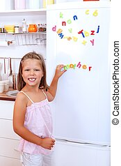 Mother - Girl with letter fridge magnets in the kitchen