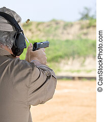 Shooter - Man using a semi automatic pistol at the shooting...