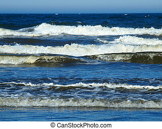 An Ocean Wave Breaking on Shore on a Sunny Day