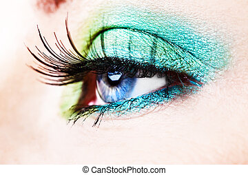 Detail of a blue eye with green eyeshade and long lashes