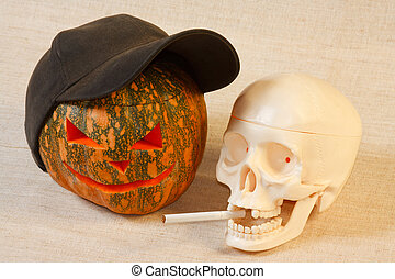 The cheerful halloween pumpkin and skull with cigarette from...