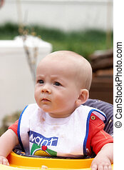 A baby frowning having just eaten his food