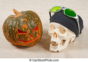 The big cheerful halloween pumpkin and skull with sigarette...