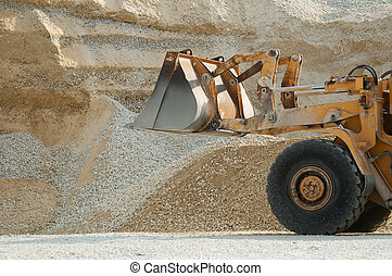Bulldozer in quarry. Huge pile of limestone and sand