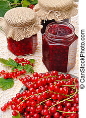 Jars of homemade red currant jam with fresh fruits