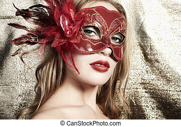 Beautiful young woman in a red mysterious venetian mask on a gol