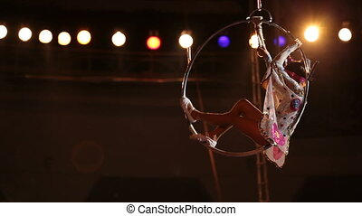 Acrobatic performance - A girl stands in the circus performs...