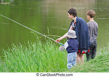 Mother and sons catch the fish on the river shore