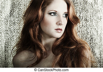 Fashion portrait of a young beautiful redheaded woman on a...