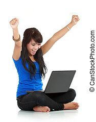 Happy and lucky young woman with laptop sitting against...