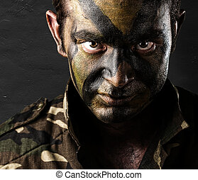 young soldier face with jungle camouflage against a grunge...