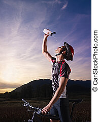portrait of man training on mountain bike at sunset - sports...