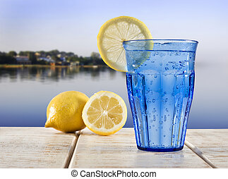a Blue glass with sparkling water and lemon on a wooden deck overlooking the calm water of a tropical lagune