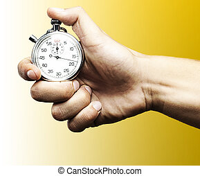 stopwatch - hand holding a stopwatch against a blue...