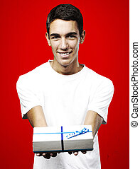 young man smiling and giving a gift against a red background