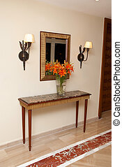 Foyer table at home entrance with flowers and mirror