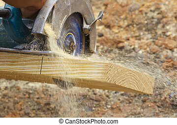 Carpenter Cutting Wood - A carpenter cutting wood using a...