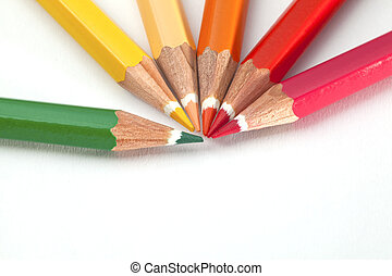 Many colored pencils on the white paper background