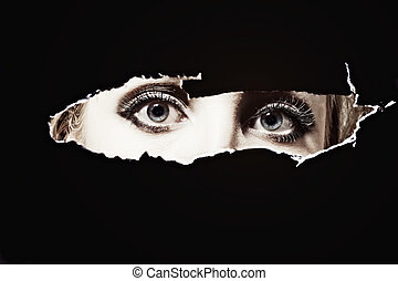 Women's blue eyes spying through a hole